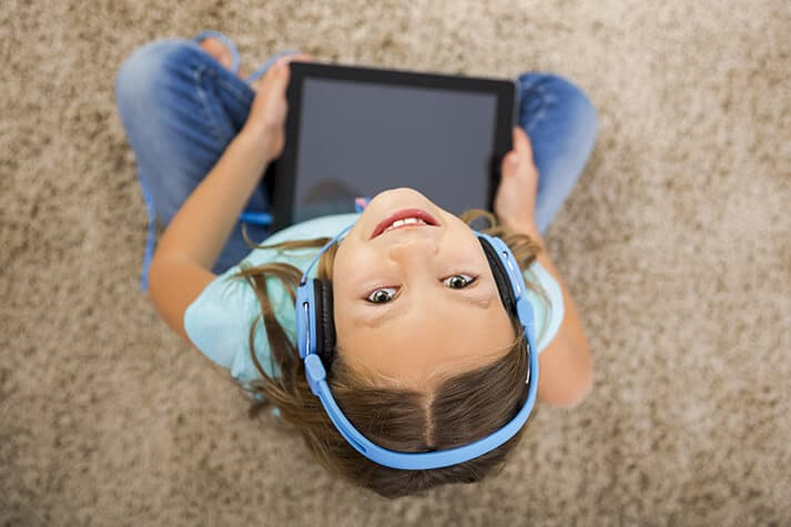 Girl on Ipad with Headphones Looking Up