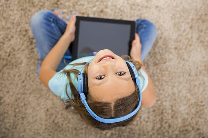 Girl on Ipad with Headphones Looking Up