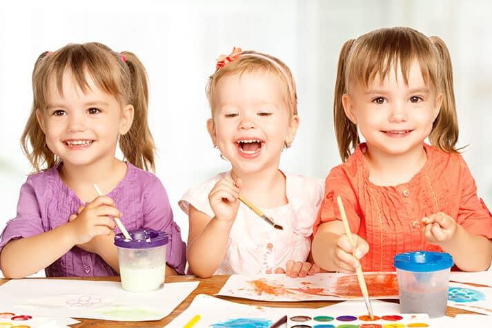 Pre-K or Preschool Kids Painting in Classroom Smiling